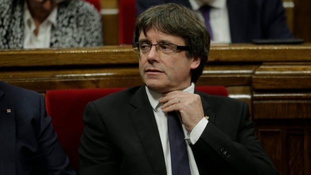 Catalan regional President Carles Puigdemont waits to make his speech at the parliament in Barcelona, Spain, on Tuesday. The Catalan president said he has a mandate to declare independence but proposes waiting 'a few weeks' to encourage dialogue.