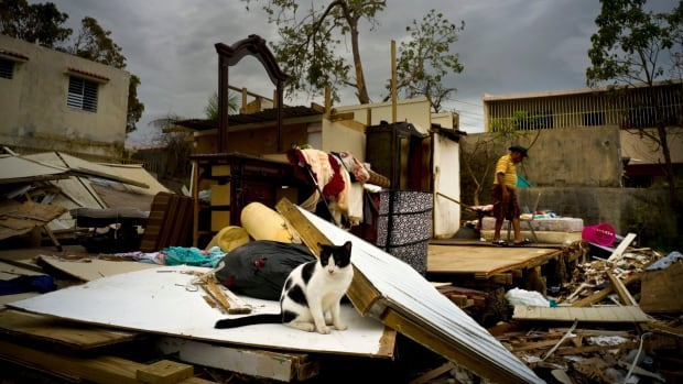 Efrain Diaz Figueroa, right, on Monday walks by his sister's home destroyed in the passing of Hurricane Maria in San Juan. Maria sent tens of thousands of Puerto Ricans fleeing to the U.S. mainland to escape the immediate aftermath of the storm.