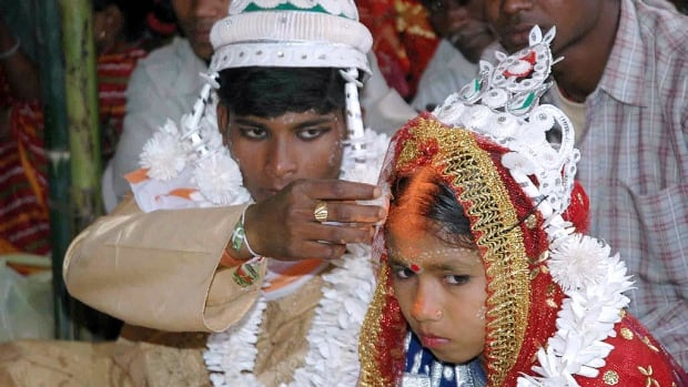 A groom puts vermilion, a Hindu sign of marriage, on the forehead of his underage bride during a mass marriage in the village of Malda, India, in March 2006.  Though illegal, child marriage is deeply rooted in India.