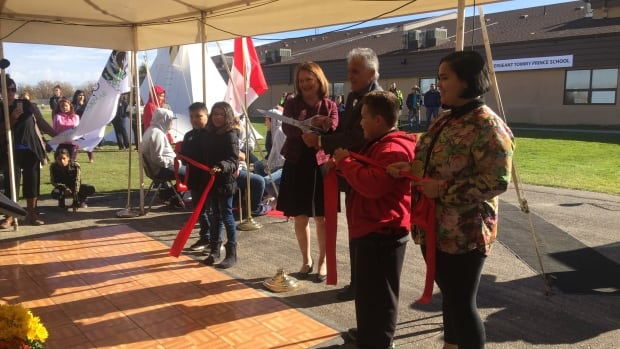 Indigenous Services Minister Jane Philpott and Lorne Keeper, the executive director of Manitoba First Nations Education Resource Centre, hold the scissors after the ribbon cutting at Sgt. Tommy Prince School on the Brokenhead Ojibway Nation.
