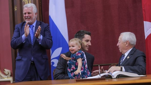 André Fortin, 35, holds his daughter as he is sworn in as minister of transport on Wednesday.