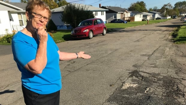 Clara McCarron points out the crumbling asphalt on her street.