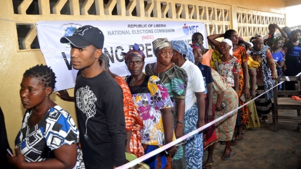 People wait to cast their votes during a presidential election at a Monrovia polling station on Tuesday. Liberians gathered in masses to vote in an election that for the first time in more than 70 years will see one democratically elected government hand power to another.