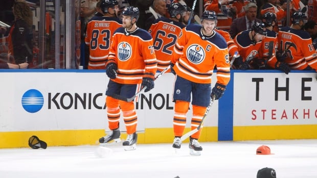 Oscar Klefbom and Connor McDavid wait for hats to be picked up off the ice after the Edmonton Oilers' captain scored a hat trick against the Calgary Flames during the season opener a week ago.