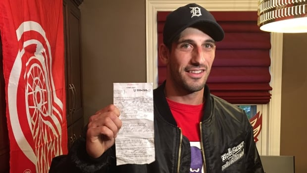 Red Wings fan Nick Horvath holds the ticket he was issued, after throwing an octopus onto the ice at the Wings' home opener.