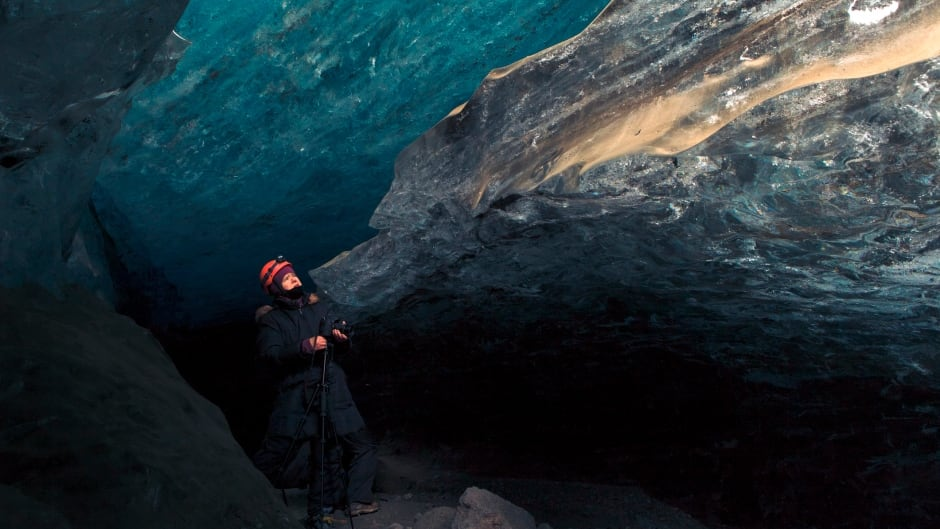 Female tourist surveying an ice cave in Iceland.