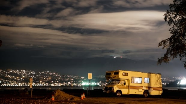 A lit up camper van at Spanish Banks beach in Vancouver, B.C. where wheeled homes often rest at night, against the backdrop of the twinkling North Shore city lights.