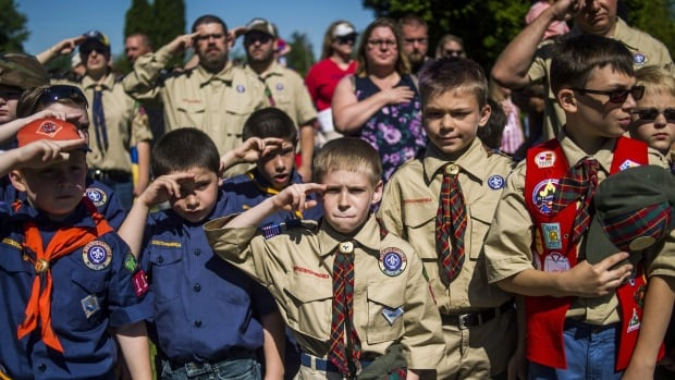 Boy Scouts and Cub Scouts salute during a Memorial Day ceremony in Linden, Mich. The Boy Scouts of America Board of Directors have unanimously agreed to welcome girls into its Cub Scout program and to deliver a Scouting program for older girls that will enable them to advance and earn the highest rank of Eagle Scout.
