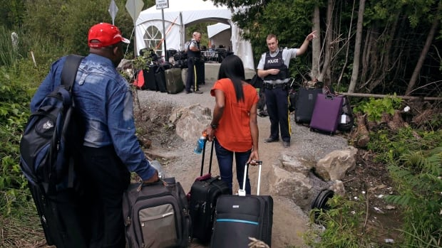 An RCMP officer speaks to people as they cross the border into Canada at Roxham Road in Hemmingford, Que., earlier this year. The RCMP created an interview guide for officers handling the asylum seekers.
