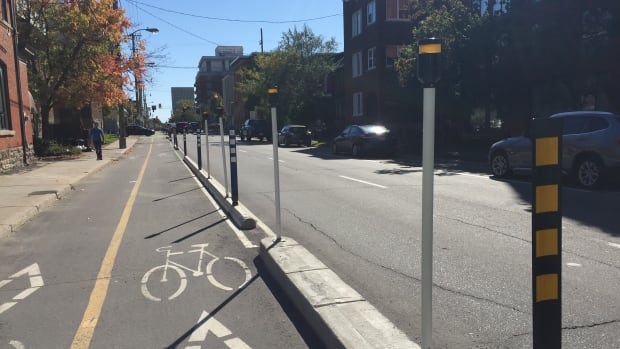 LED lights mounted on white poles will flash in response to cyclists moving through the intersection of O'Connor Street and Waverley Street in the bike lane. Within weeks of the bike lane's official opening, two cyclists were struck by left-turning vehicles.