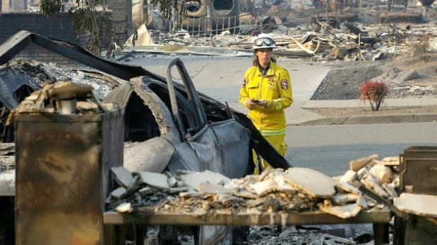 Cal Fire forester Kim Sone inspects damage at homes destroyed by fires in Santa Rosa, Calif., on Thursday.