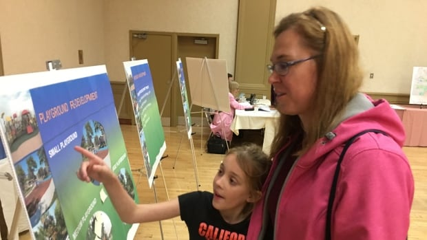 Christina Konopaski checks out playground designs with her daughter Annika at the City of Windsor Park Improvement open house Thursday night.