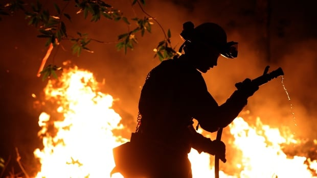 Firefighter Trevor Smith works near near Calistoga, Calif., on Thursday. At least 31 people have died in wildfires that have destroyed about 5,700 homes and businesses in several Northern California counties.