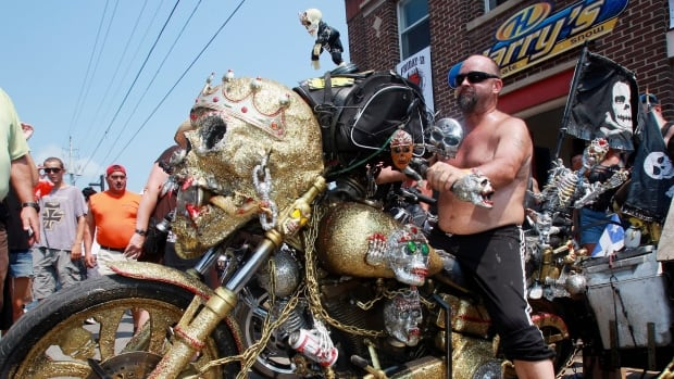 Danny Fournier of Montreal poses with his skull covered motorcycle in Port Dover, Ont., Friday, July 13, 2012. Under sunny skies, a Friday the 13th tradition is rolling along in the small town of Port Dover, Ont. Police estimate that by mid-morning, about 120,000 people, many on motorcycles, had descended on the town on the shores of Lake Erie, to take part in the last BikeFest of the year.