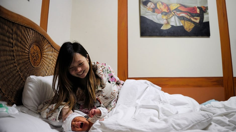 A mother and her baby on a bed in a maternity ward at Antai Hospital in Beijing.