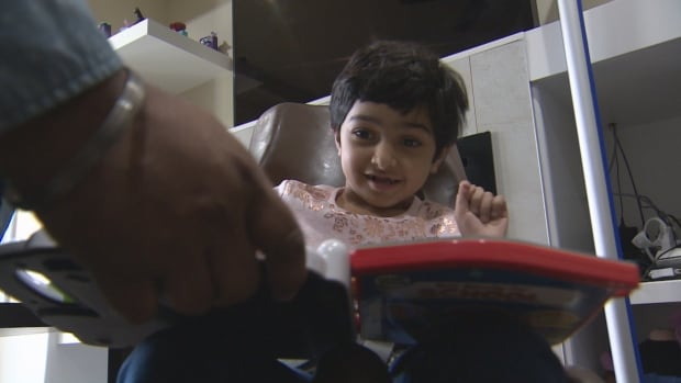 Amber Athwal sits in a chair in her home as her father encourages her to repeat the names of colours on a toy.