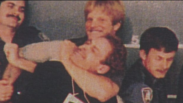 A close-up of the infamous 1982 Vancouver police line-up photo, showing Ivan Henry in a headlock