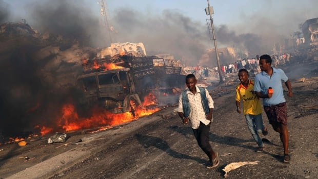 Civilians flee from the scene of the explosion in KM4 street in the Hodan district of Mogadishu, Somalia.
