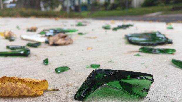 A lone smashed bottle sits on Preston Street, one of the streets where a series of homecoming parties were held and then shut down Saturday.