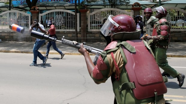 A riot policeman fires tear gas to disperse supporters of Kenyan opposition National Super Alliance (NASA) coalition during a protest along a street in Nairobi on Monday.