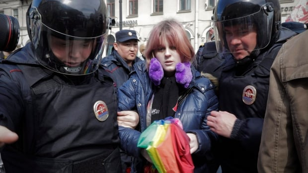 In this Monday, May 1, 2017 file photo, a gay rights activist holding a rainbow umbrella is detained by police during a rally marking May Day in downtown St. Petersburg, Russia.
