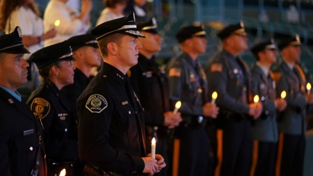 Camden County Chief of Police Scott Thomson, centre, along with officers from other agencies, participate in a candlelight vigil in remembrance of those who have died from drug overdoses on Saturday in Camden, N.J.
