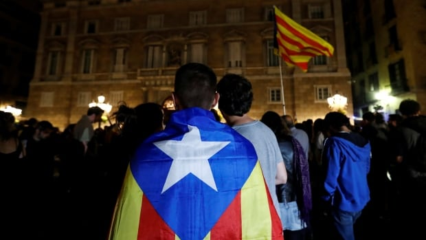 A man wears an Estelada, the Catalan separatist flag, as protesters gather outside the regional government headquarters after Spain's High Court jailed the leaders of two of the largest separatist organizations, in Barcelona on Monday.