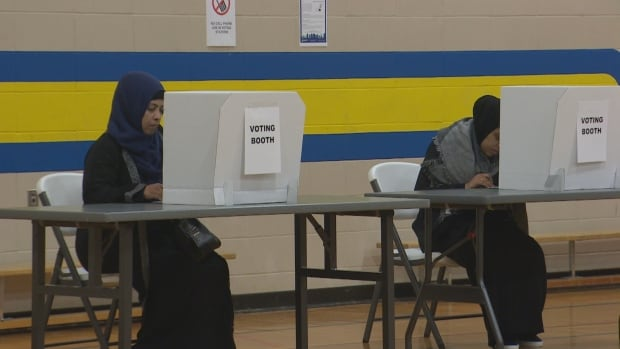 Muna Ahmed [right] fills out her ballot in the gymnasium of Kirkness School.