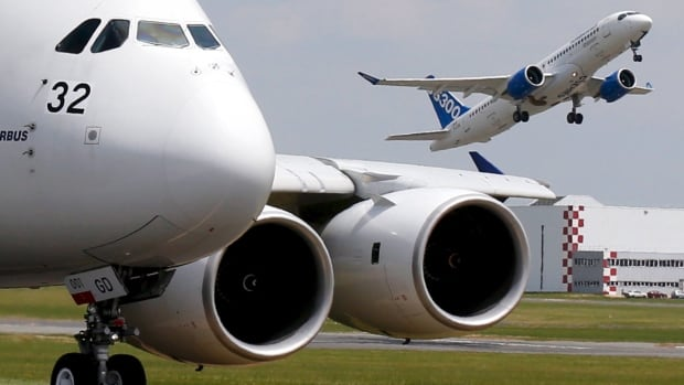 A Bombardier CS300 aircraft takes off to participate a flying display as an Airbus A380, the world's largest jetliner, waits on the taxiway during the 51st Paris Air Show at Le Bourget airport near Paris, in this June 2015 photo.