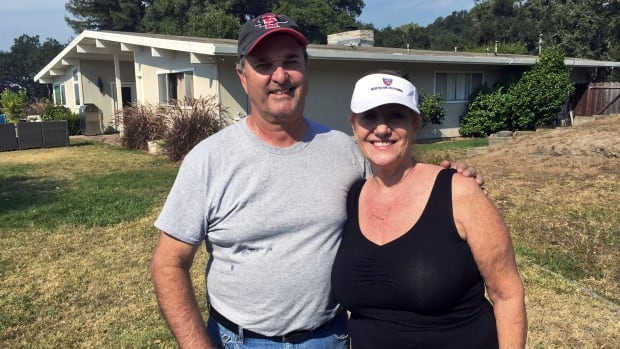 Tom and Catherine Andrews pose at their home in Santa Rosa, Calif., on Monday. On one side of their mid-century style home, the deadly wildfires that ravaged parts of Northern California for more than a week wiped away the houses of neighbours they have known as long as two decades.
