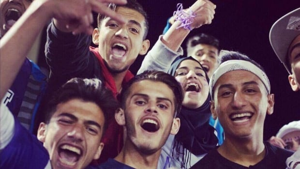 Moiad (Mo) Alhamoud, in the white headband, was excited to go to the Moncton High football game to cheer for the team with his brother and friends.