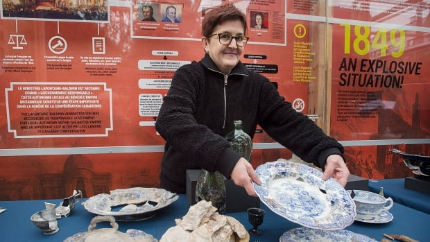Louise Pothier, chief archaeologist at the Pointe-à-Callière museum, holds an artifact taken from the site of the old parliament of the United Province of Canada during a news conference in Montreal on Tuesday.