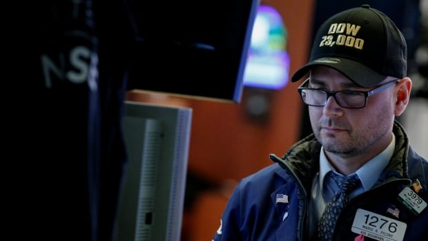 Trader Mario Picone wears a Dow 23,000 hat, moments after the stock grouping briefly hit the benchmark.