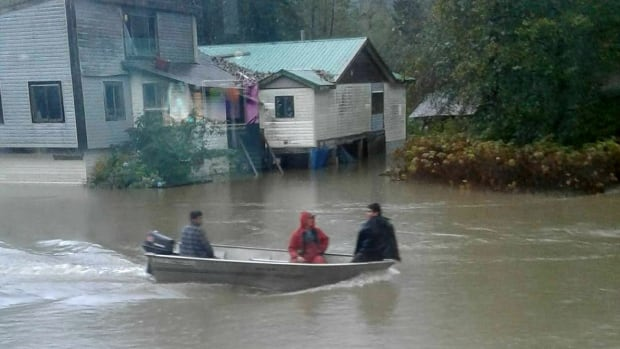 People travelling by boat in the floodwaters on Oct. 17, 2017.