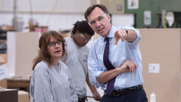 Finance Minister Bill Morneau, right, chats with a worker at a kitchen counter factory, in Montreal on Tuesday.