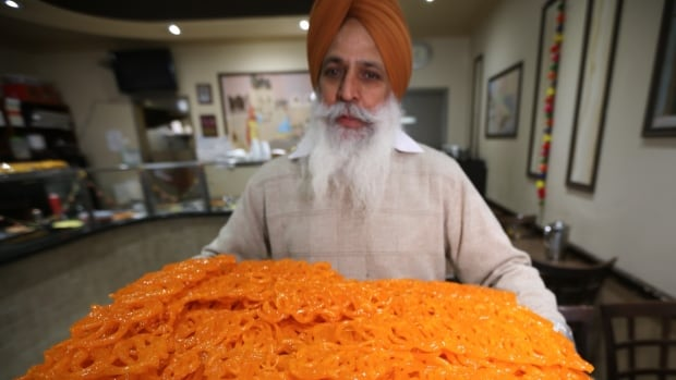 Tarlochan Singh holds a tray of popular treats - jalebi - at Bengali Sweets in Etobicoke. Singh said they've spent days preparing for the influx of customers for Diwali.