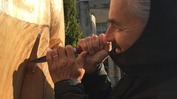 Haida carver James Hart puts the finishing touches on the reconciliation totem pole he oversaw the creation of, installed at UBC's Point Grey campus in the spring.
