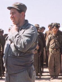 Donald Nichols inspecting parachute unit of Korean men