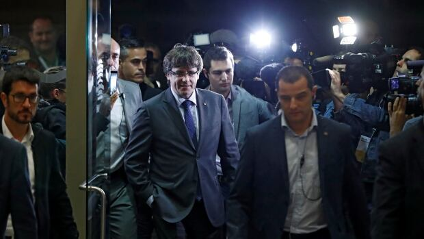 Catalan President Carles Puigdemont, centre, arrives to attend the Catalan European Democratic Party extraordinary national council meeting in Barcelona on Wednesday. He told party members he would press ahead with a more formal declaration of independence if Madrid suspends Catalonia's political autonomy.