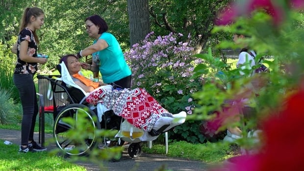 Diana Fitzharris relaxes in the May Court hospice garden with daughter Gwendolin, left, and best friend Lydia Wang.