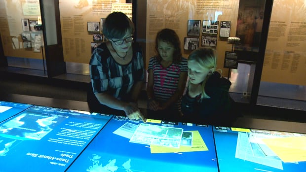 Laura Secord School teacher Jackie Cleave shows students Leah Mackinnon, centre, and Cooper Johnson, right, some of the displays about residential schools at the Canadian Museum for Human Rights.