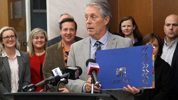 "Mayor Fred Eisenberger showed off the Amazon bid book, and a video with the ""We are unstoppable"" slogan, at city hall Thursday."