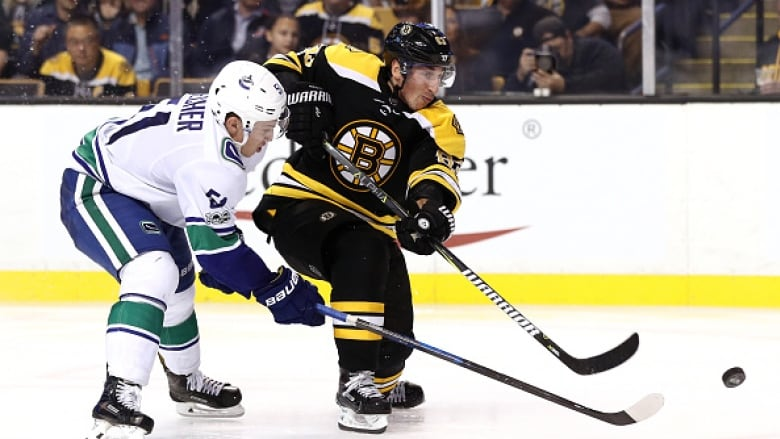 1fbd0233f9b Brad Marchand, right, of the Bruins shoots as Troy Stecher of the Vancouver  Canucks attempts to defend during Boston's 6-3 win on Thursday.