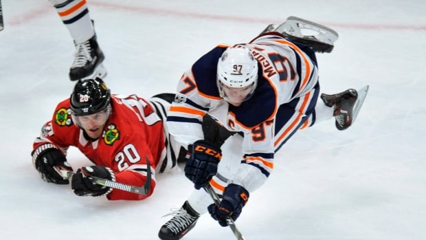 Connor McDavid of the Oilers reaches for the puck as Brandon Saad of the Chicago Blackhawks falls to the ice during Edmonton's 2-1 OT win on Thursday.