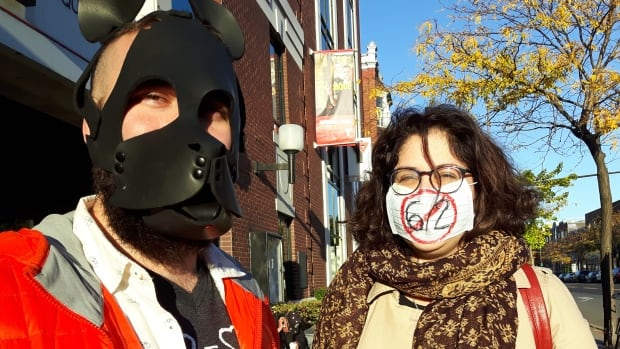 People covering their faces waited at bus stops along Parc Avenue in Montreal to protest Bill 62.
