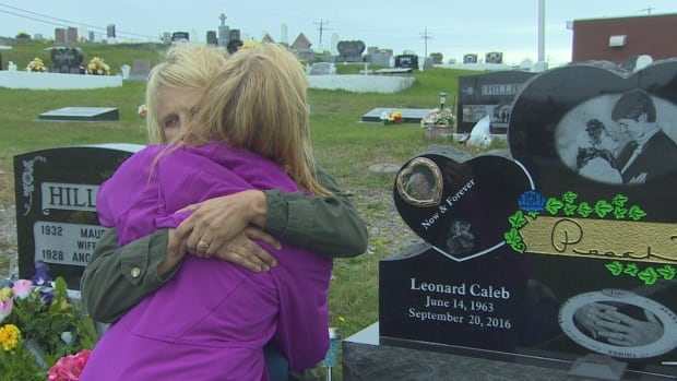 Natalie Randell hugs her sister, Valerie Peach, by Leonard Peach's grave. Both sisters lost their husbands to suicide in Grand Bank.