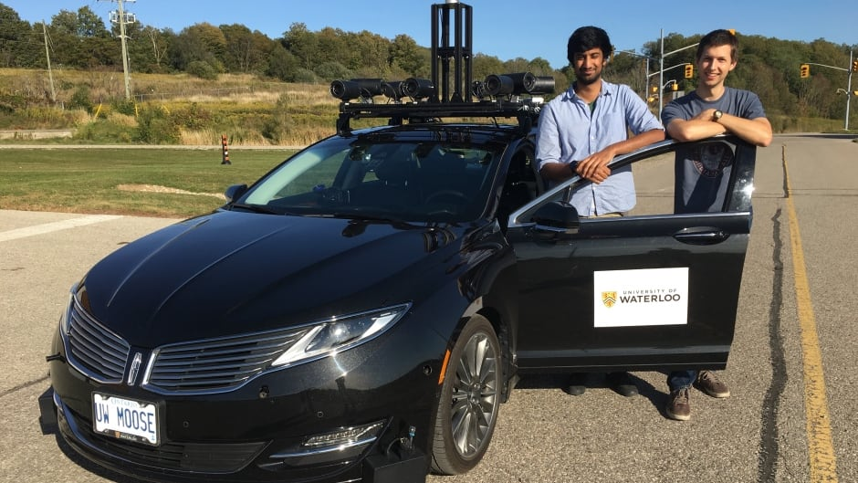 University of Waterloo master's students Nav Ganti and Ian Colwell stand with the 'Autonomoose' self-driving car.