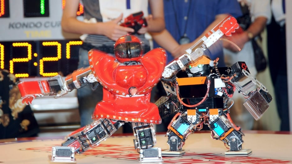 """Remote-controlled robot named  """"Arikion"""", left, fights opponent robot during a humanoid battle match at a shop in Tokyo's main electronics district of Akihabara."""