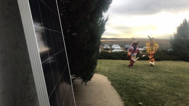 Two youngsters dance near a solar panel to be installed at Louis Bull Tribe's community daycare centre Friday.