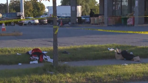 Clothing is left scattered on the ground after a stabbing injured three teens in Scarborough on Friday. Toronto police are looking for two male suspects who were last seen fleeing the area on a motorcycle. Police have not determined what led to the stabbing and they have not recovered the knife.